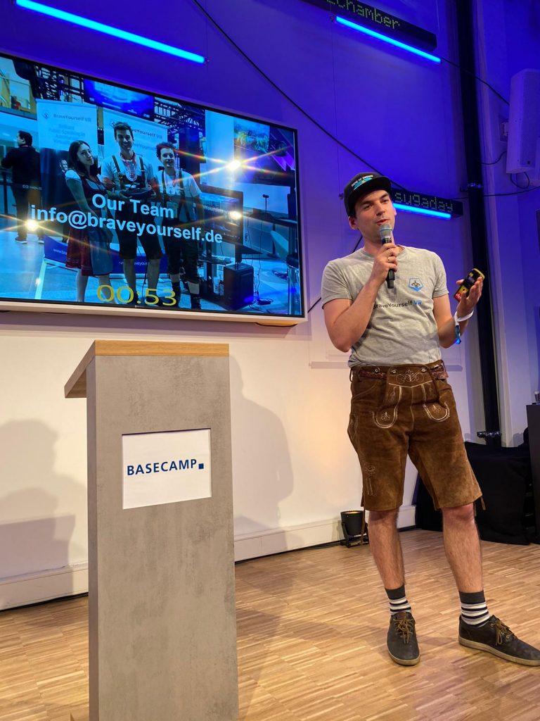 Max Aigner steht auf der Bühne von BaseCamp in Berlin und präsentiert Game of Drones und die Zukunft des Sportes mit 5G